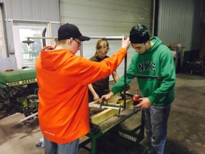 Sabastian Vanderport, Emily Tarala, and Cody Kirkeide work together to build the cart that will haul the robot from the pits to the arena at the competition.