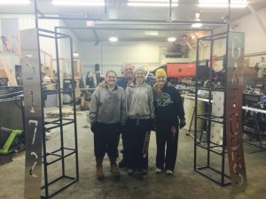 Abbie Brockhouse, Hannah Anderson, and Morgan Anderson happily pose with their welding project.  Mentor, Don Brekke, worked with them to create this stand that will be placed at our pit entrance.