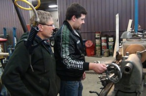 Martyn Novacek operating the turning lathe while mentor Doug Hlucny assists.